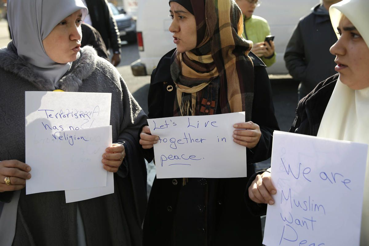 Amina Ismail, left, Fatima Amaziane, center, and Dalia Abdallah hold signs during a news conference in the Queens borough of New York, Thursday, Dec. 10, 2015. The news conference was called to express opposition to hate crimes and rhetoric, particularly