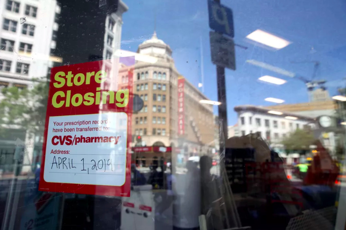 A sign is posted on the window of a closed CVS store on Market Street.