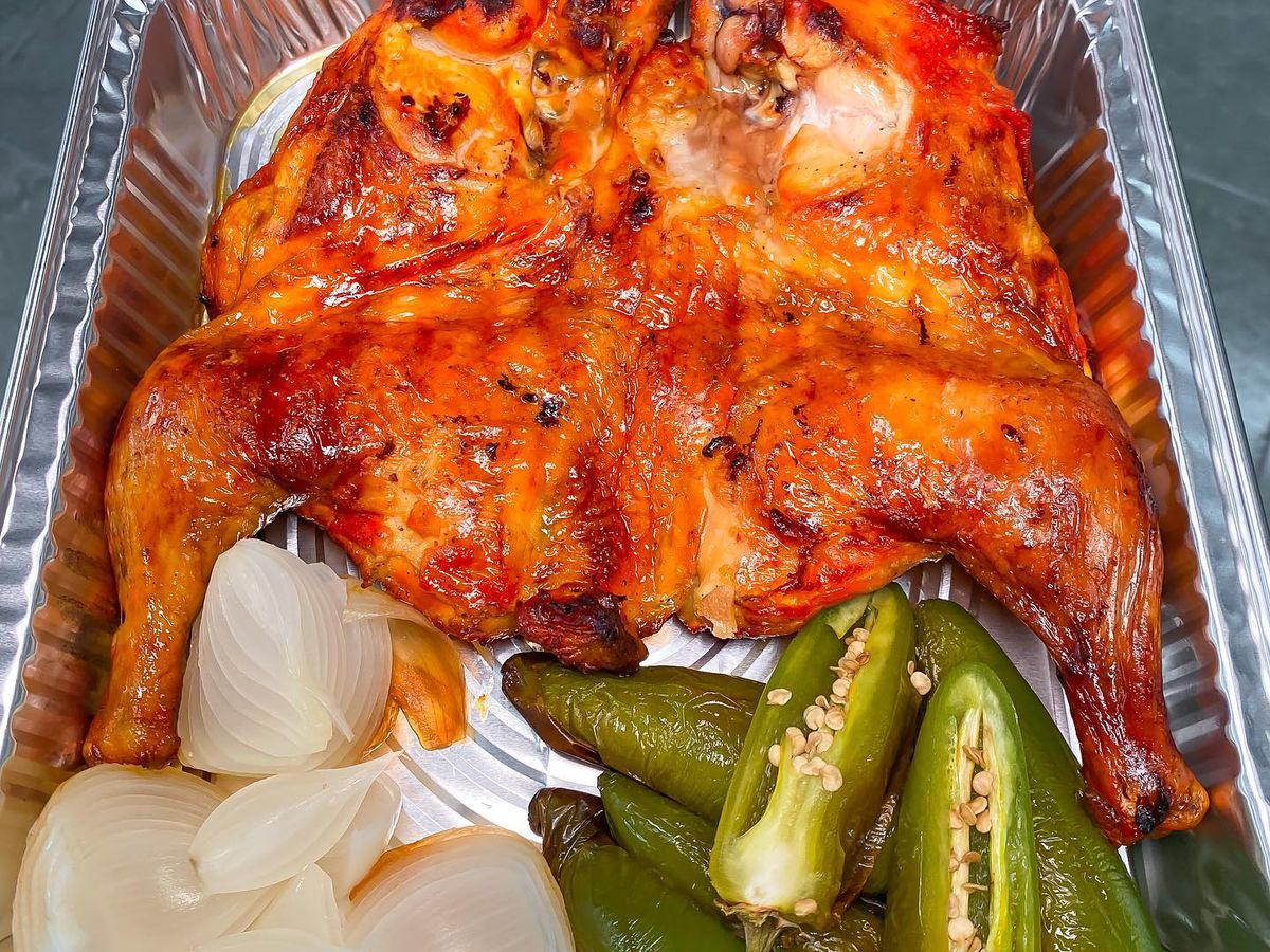 A silver tray with pollo asada, onions and peppers