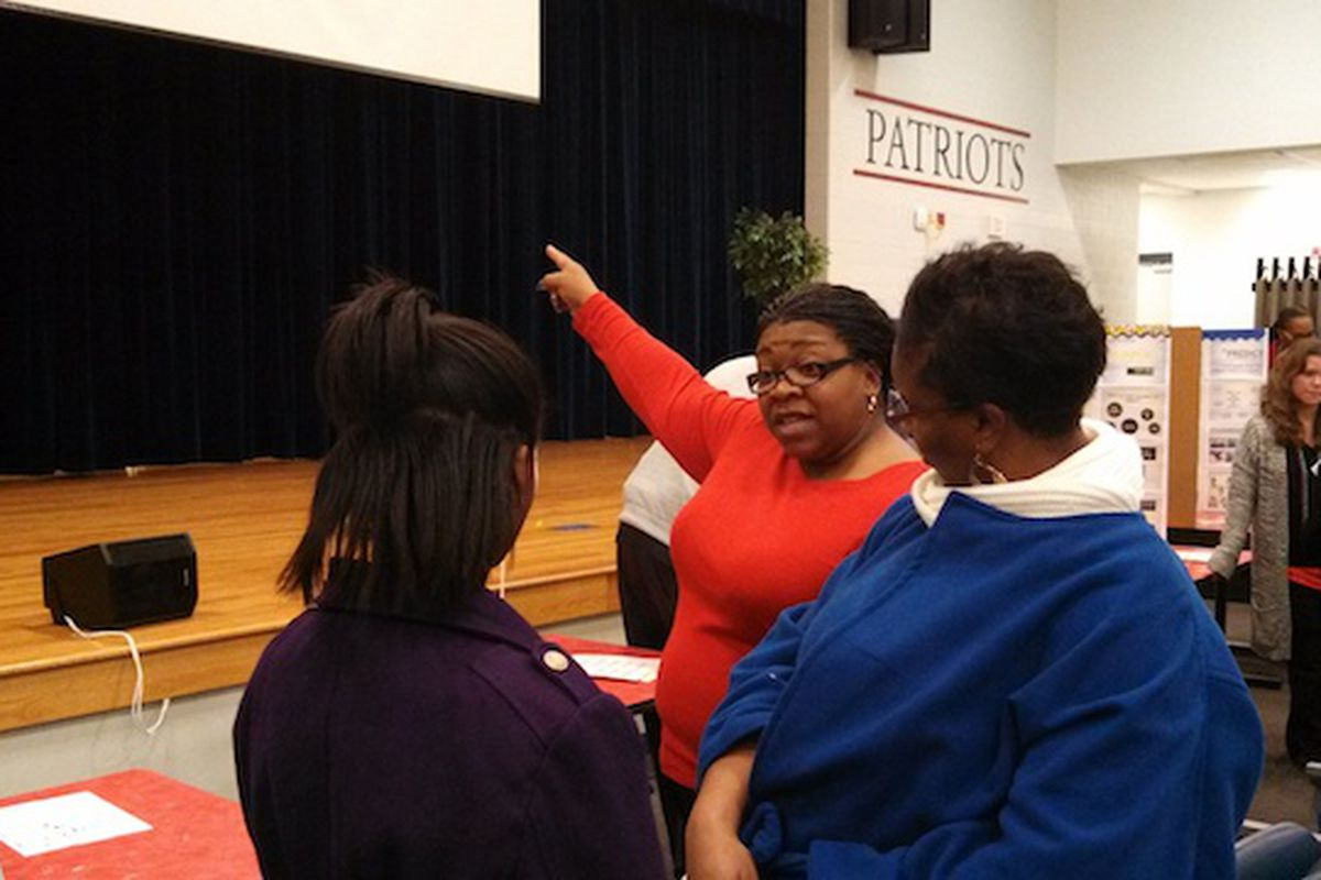 Colonial MIddle language arts teacher Patricia Hervey talks to student Ayante Williams and her mother, Sharon Kuykendall, about creative arts high school options.