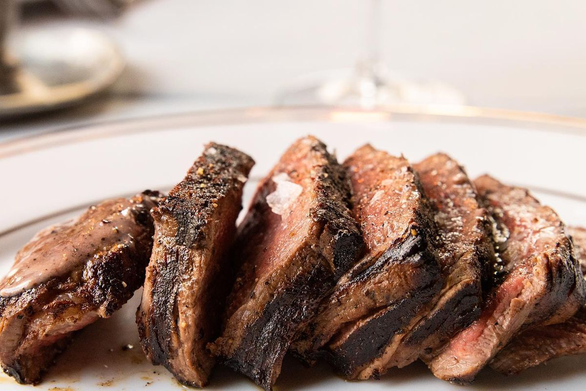 a steak sliced into rounds on a table with a wine glass and white tablecloth