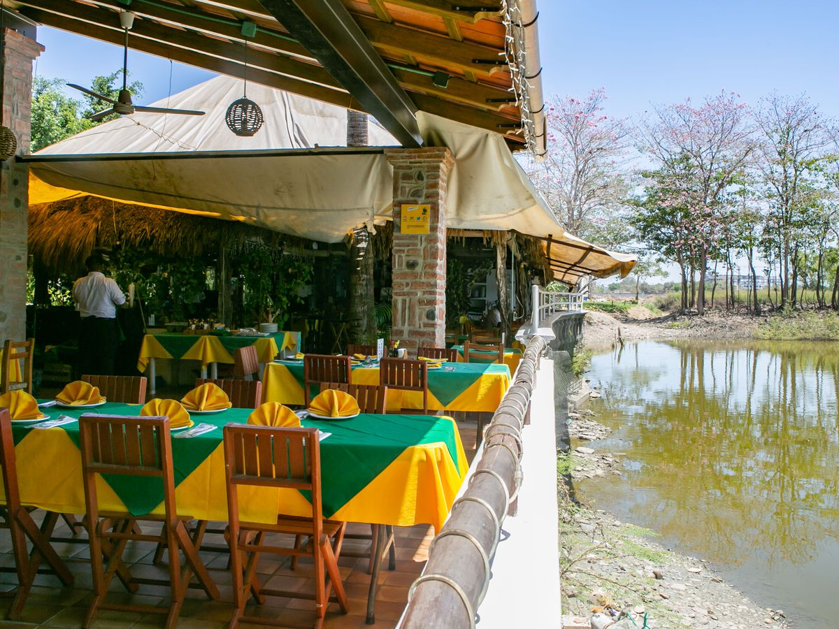 A patio with colorful tables is next to a lake.