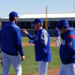 Kris Bryant, an unidentified coach, and Joe Maddon