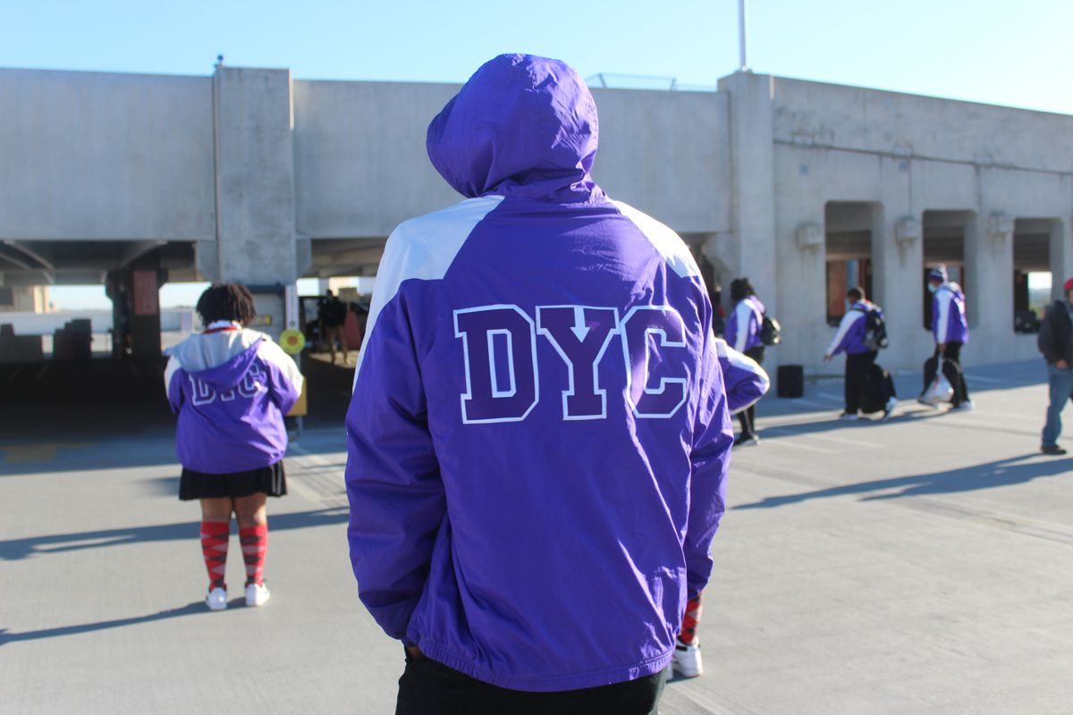 """Teenagers walk through a parking garage, all wearing purple and white hoodies with the letters """"DYC"""" on the back."""