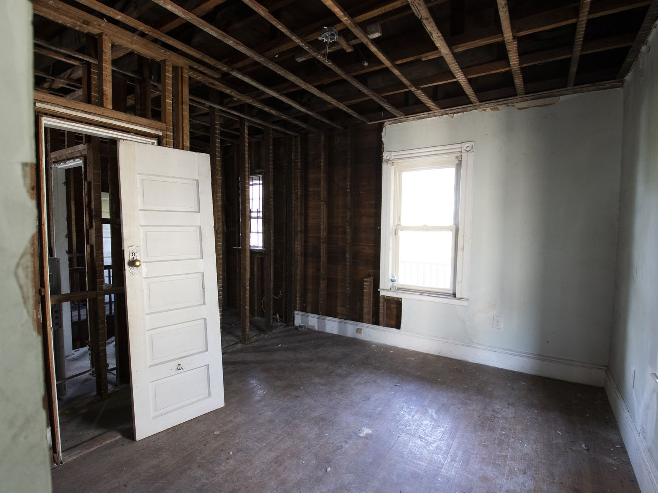 The interior of a house featured on This Old House  Season 42 that sustained fire damage. The left side of the room has all of the drywall removed and a door off of its hinges.