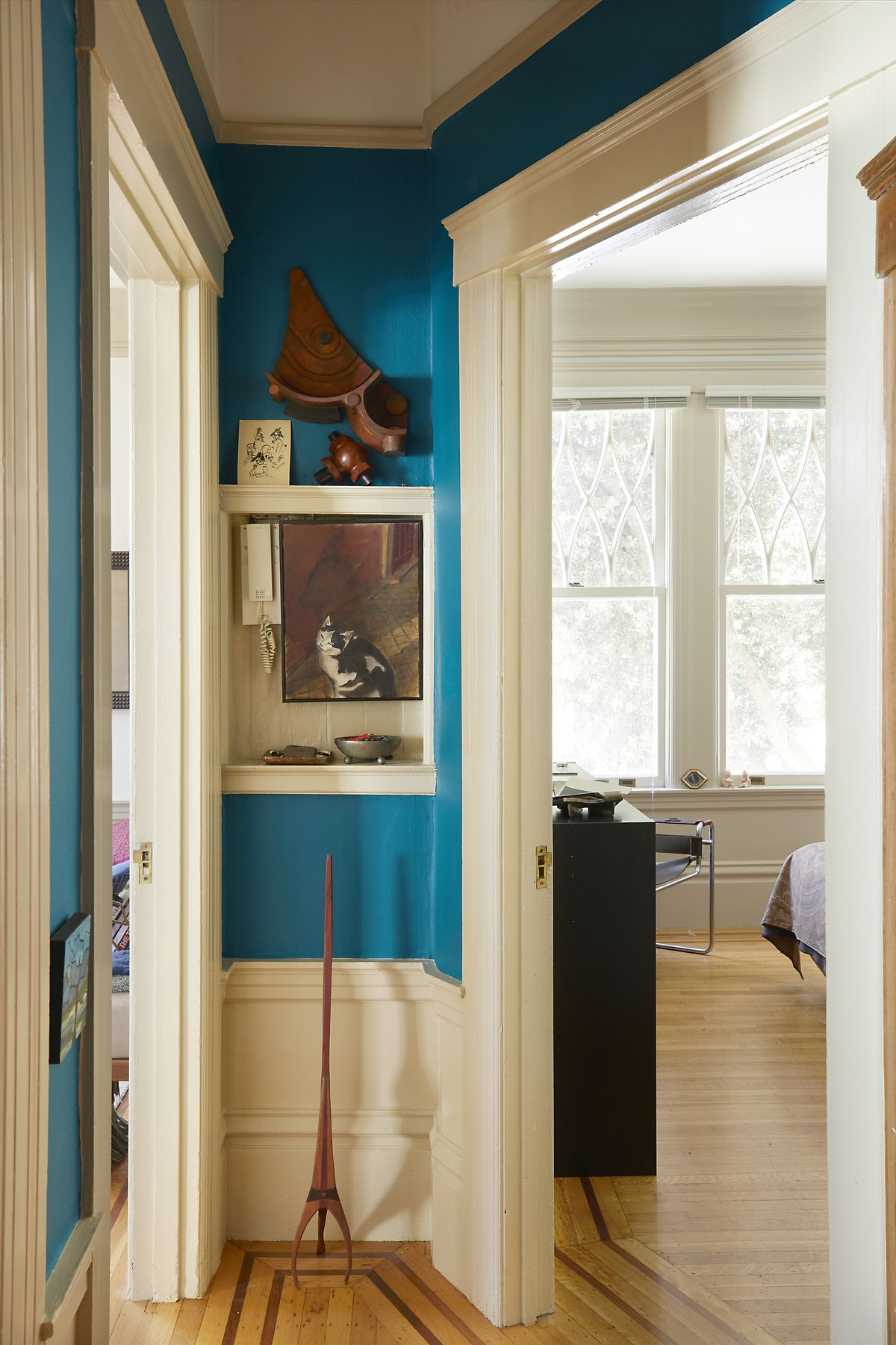 The corner of a hallway. The wall is painted blue. The moldings are white. There are multiple works of art hanging on the wall. The doorway looks into a bedroom. The floor is hardwood.