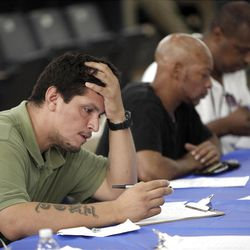 Job seekers fill out applications at a job fair in New York in August. The Labor Department's latest report didn't offer them much hope.
