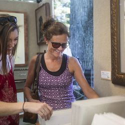 Carly Child, left, and her mother, Wendy Child, peruse through the stacks of art in Michael Rohner's booth on the first day of the Utah Arts Festival in Salt Lake City on Thursday, June 22, 2017. Carly bought a piece of Rohner's art in a gallery in San Francisco years ago.