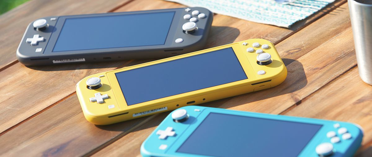 Three Nintendo Switch Lites laying on a table. One is yellow, one is grey, and the other is turquoise.