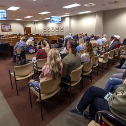 People sit in overflow areas during the Legislature's Business and Labor Interim Committee at the Capitol in Salt Lake City on Monday, Oct. 4, 2021. Several hundred people showed up at the meeting to express their opinions about the Biden administration's COVID-19 vaccine mandate.