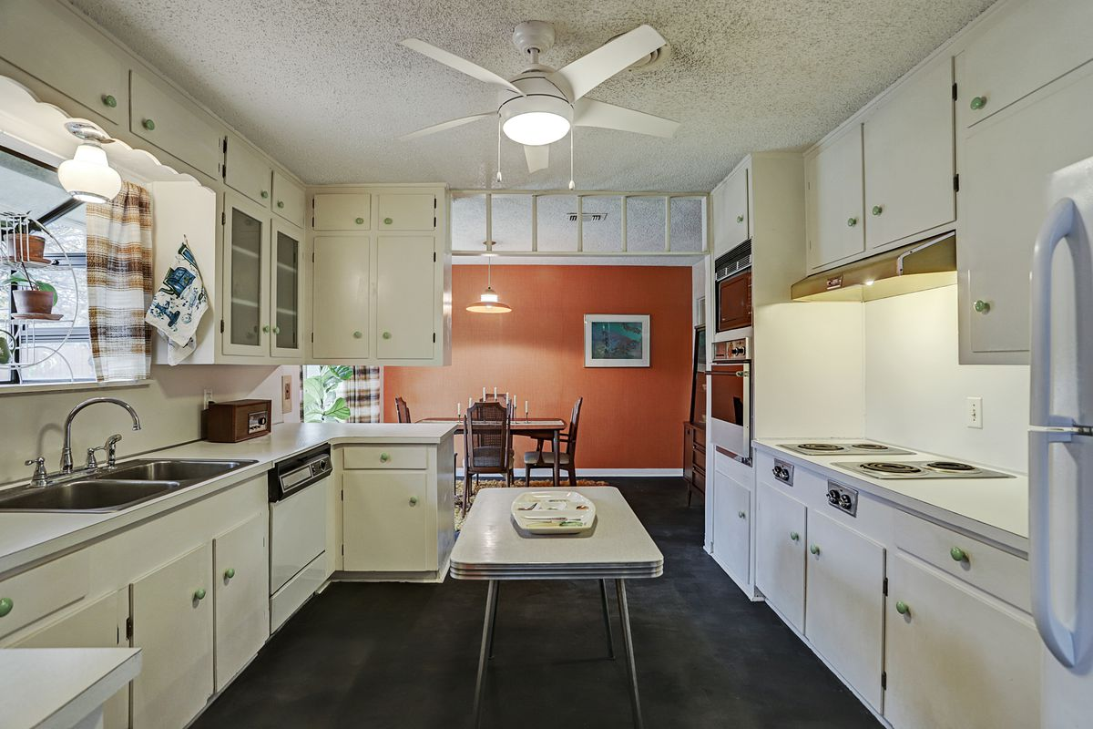 An all-white 1950s kitchen with a vintage cooktop and a small table in the middle that functions as an island.