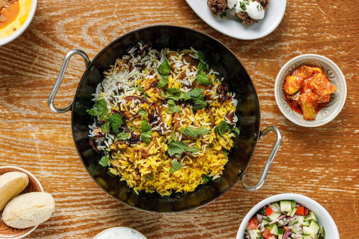 A Parsi biryani shot from above in a cast-iron bowl