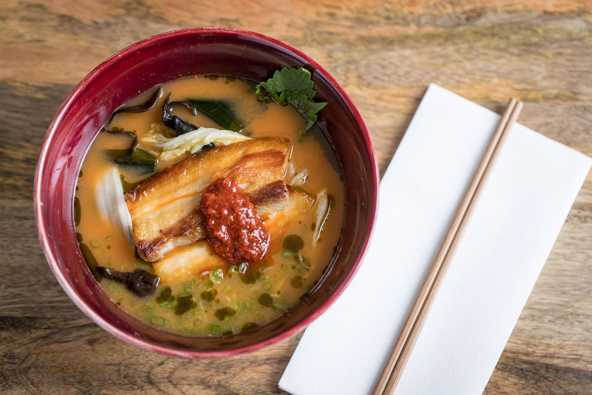 A red bowl of noodle soup is topped with slices of pork and accompanied by a white napkin and wooden chopsticks.