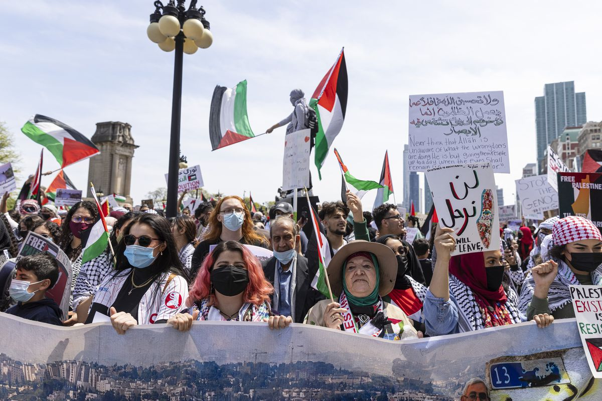 Supporters hold up flags and posters during a rally and march in support of Palestinians at Congress Plaza Garden in the Loop in response to an ongoing assault between Israelis and Palestinians in the middle east, Sunday, May 16, 2021.   Anthony Vazquez/Sun-Times
