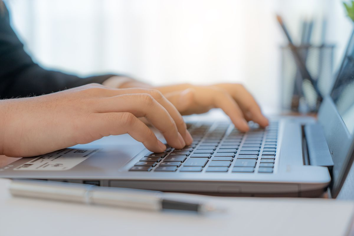A person types on a laptop.