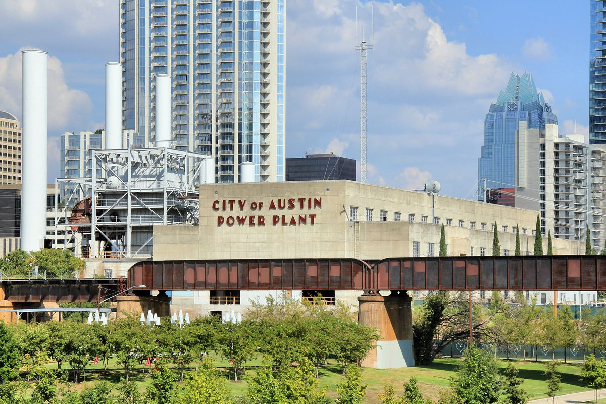 """A concrete Art Deco building that says """"CIty of Austin Power Plant"""" with Austin skyline in background"""