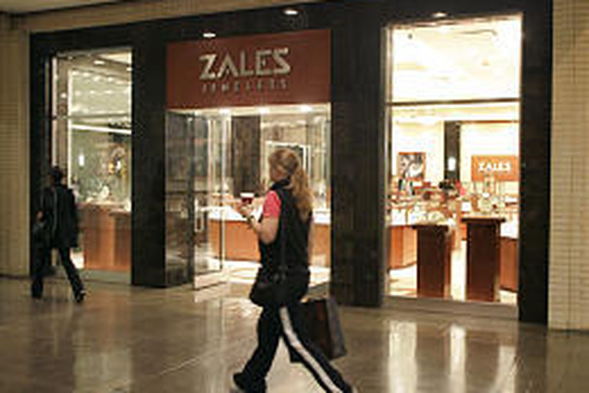 Shoppers walk past a Zales Jewelers in Dallas. The retailer reported a wider loss for the quarter.