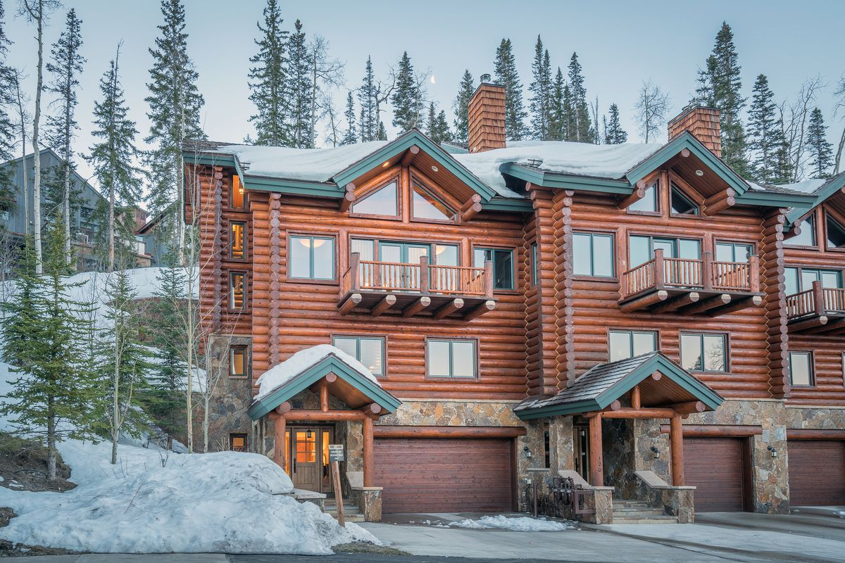 A log cabin and stone set of condos features green trim, balconies, and garages. Snow and trees surround the building.