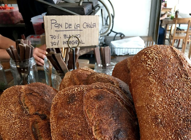 Loaves of bread sit a cafe counter with a hand-written sign bearing prices.
