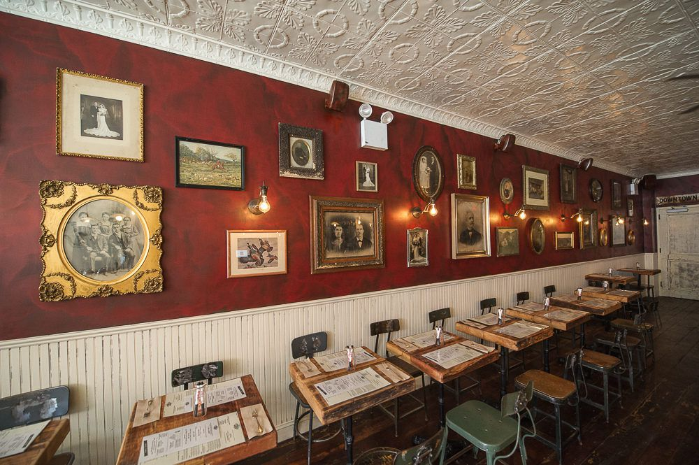 Red wall with picture frames and wooden dining tables and green chairs at the Meatball Shop
