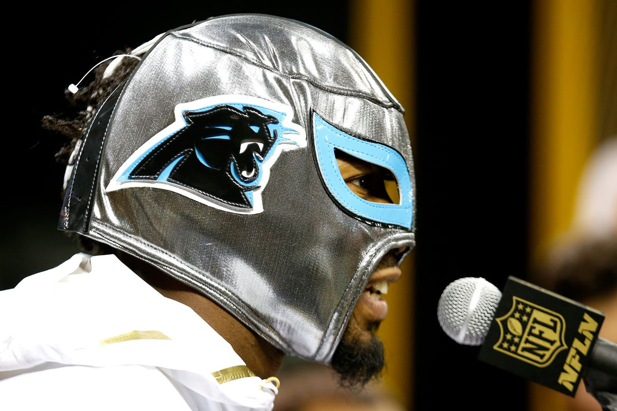 A masked Josh Norman addresses the media on Super Bowl Opening Night