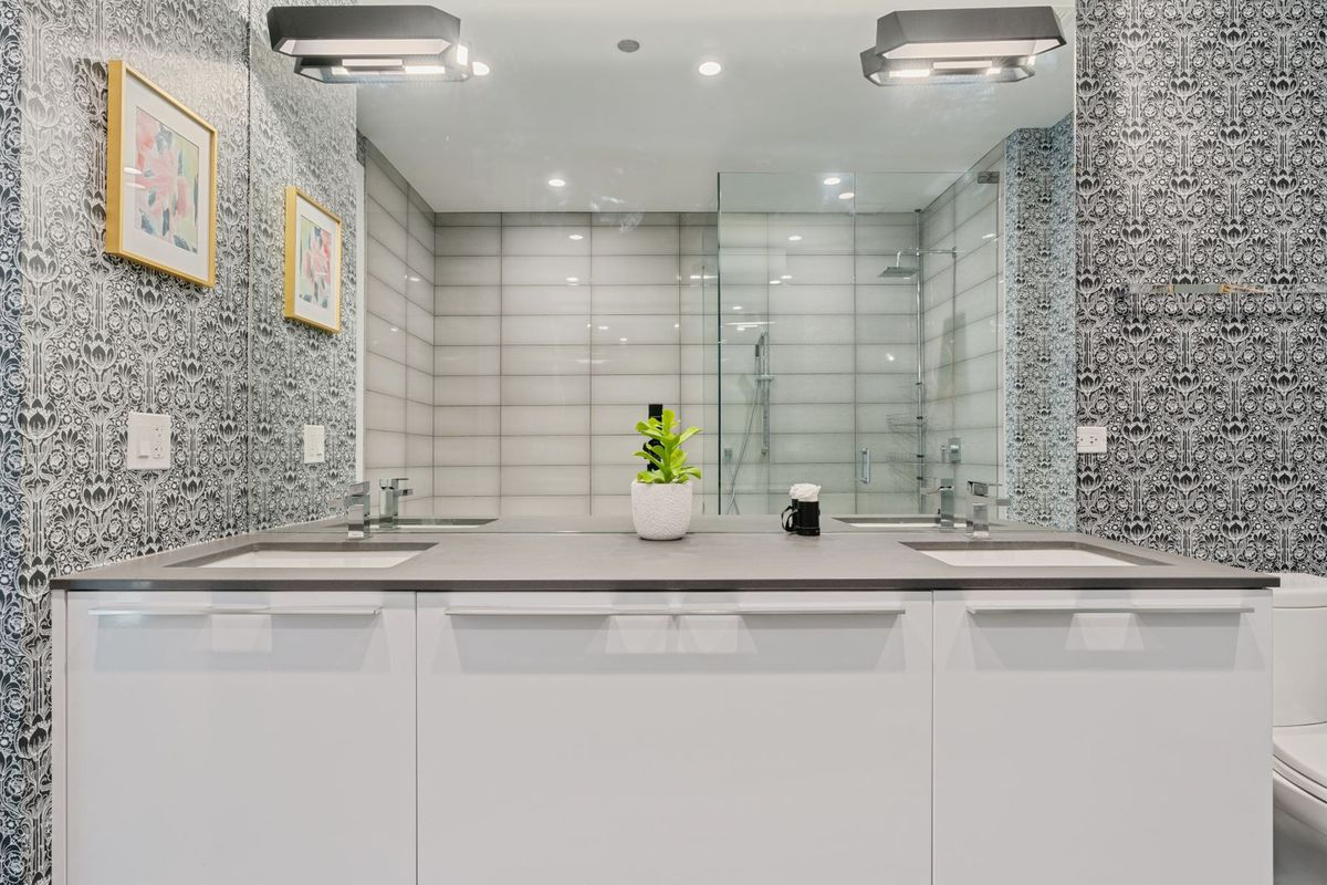 A bathroom with a double vanity, large mirror, black and white wallpaper, and a glass walk-in shower.