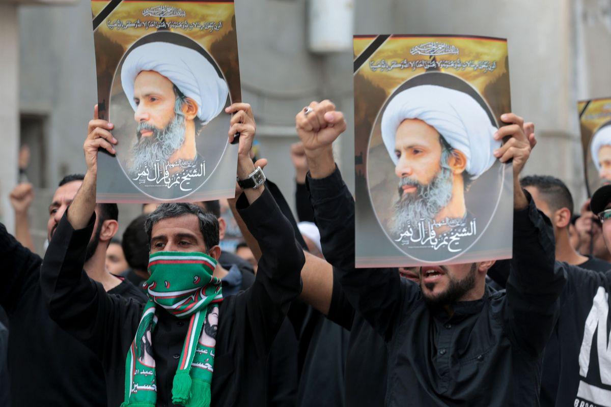 Saudi Shia men hold placards bearing portraits of prominent Shia Muslim cleric Nimr al-Nimr during a protest on January 8, 2016, in the eastern coastal city of Qatif against his execution by Saudi authorities earlier in the week.