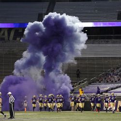 Washington players run out of a tunnel through a cloud of purple smoke in front of empty seats at Husky Stadium before an NCAA college football game against Utah, Saturday, Nov. 28, 2020, in Seattle. Due to the COVID-19 pandemic, no fans were in attendance at the game.