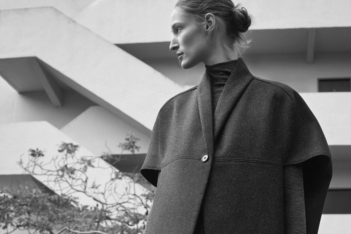 A woman wears a voluminous coat with a single button over a turtleneck sweater in front of a building with white exterior staircases.