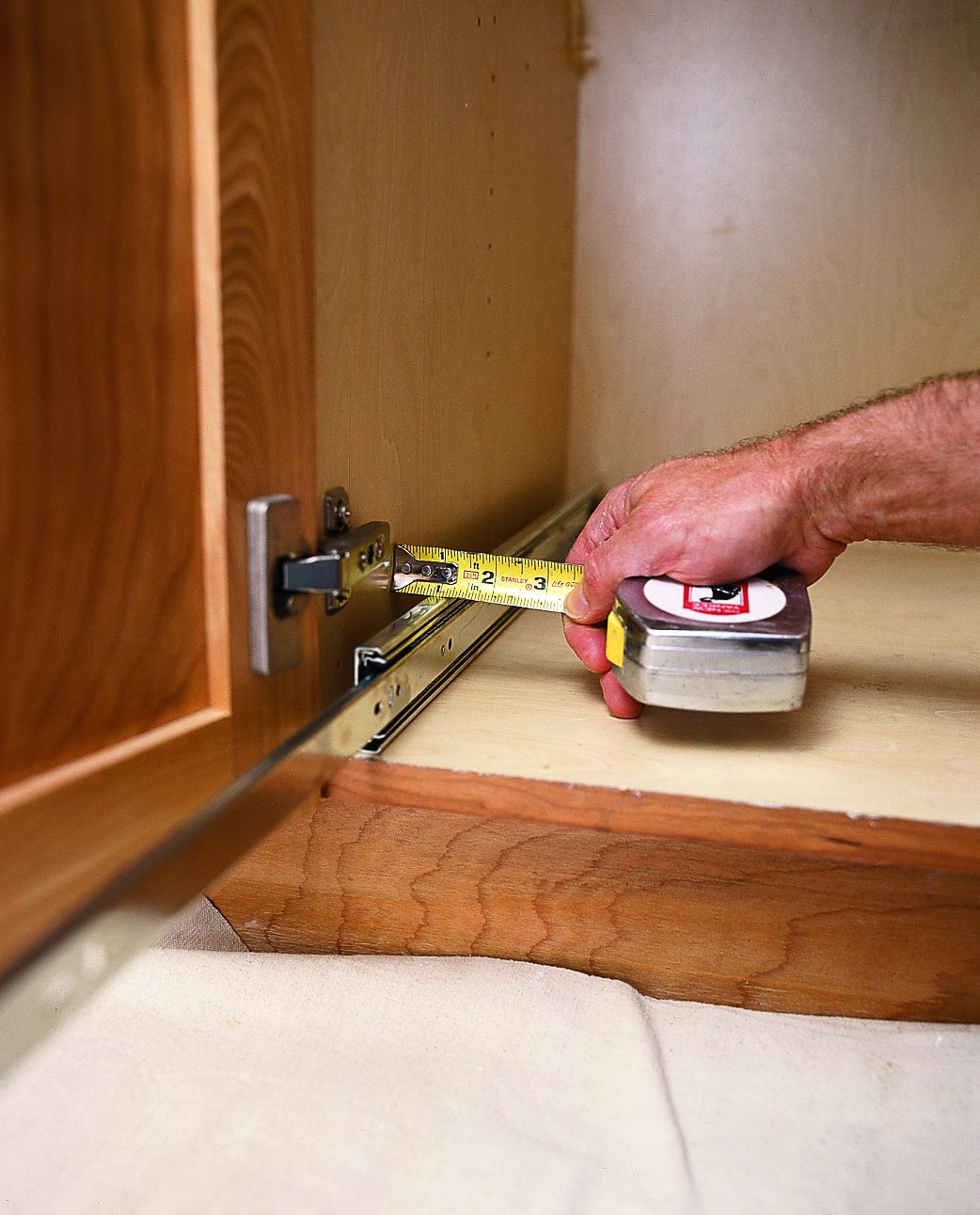 Man Measures Kitchen Cabinet With Tape Measure  For Pull Out Shelves