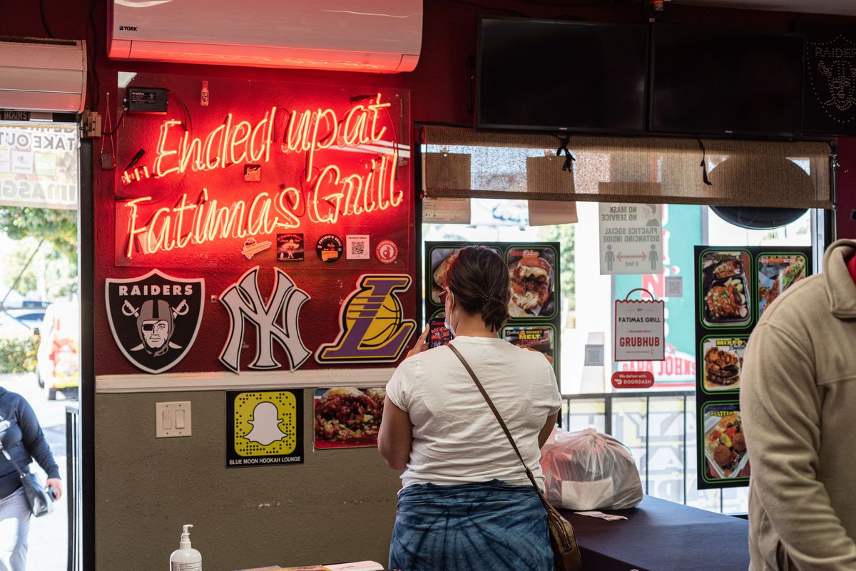 A customer, back turned, waits inside a restaurant briefly, as a neon side glows on.