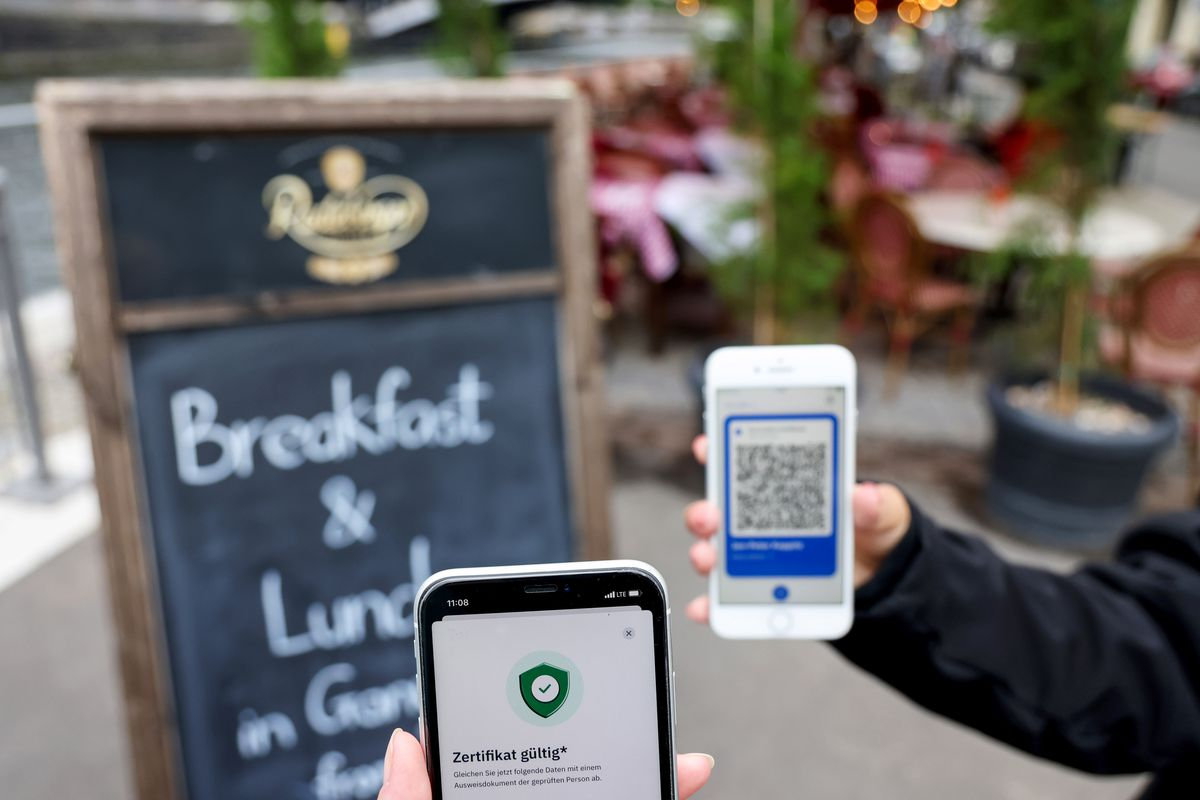 A restaurant patron holds up their phone with a QR code so the host can scan it with their phone.