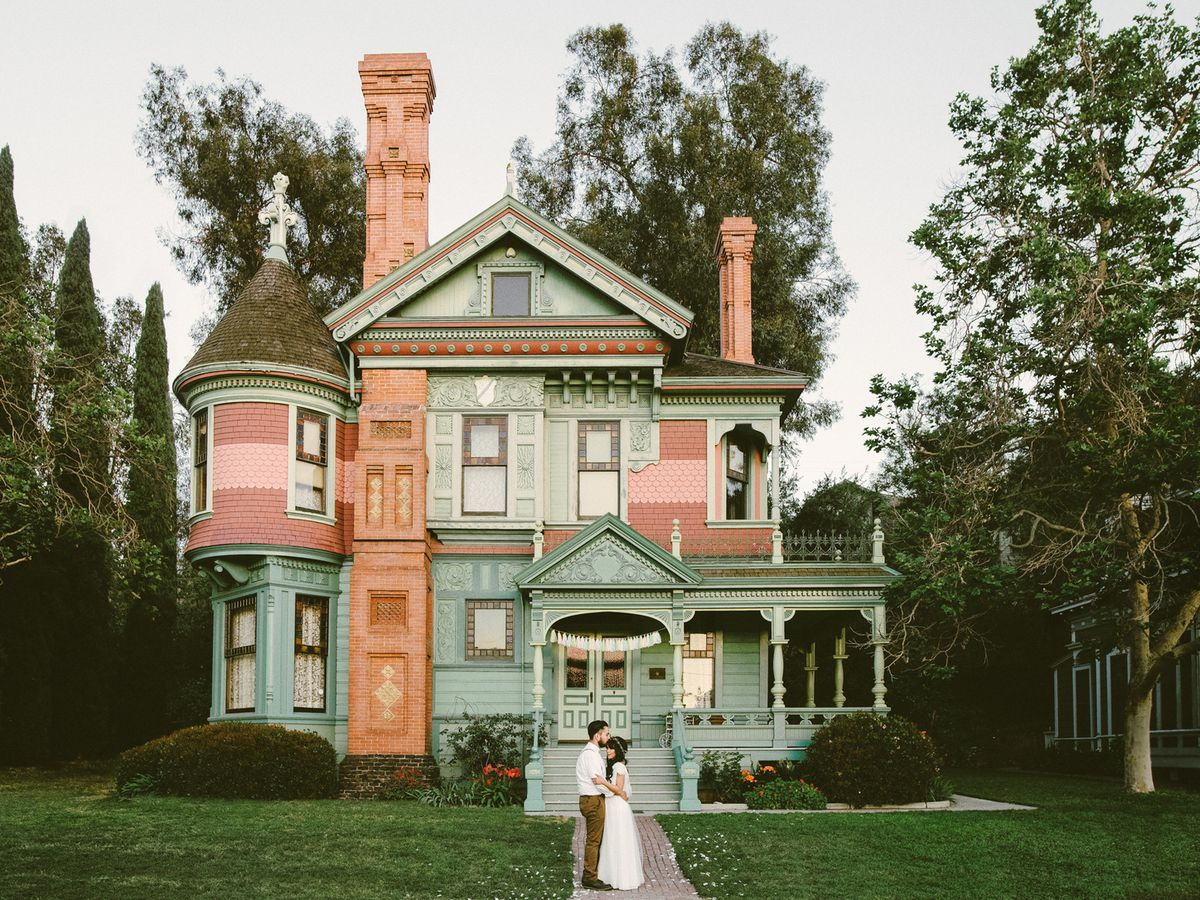 A just-married couple in a white wedding dress and suit are in front of the Hale House at Heritage Square Museum. The house is multicolored and has a chimney and a tower.