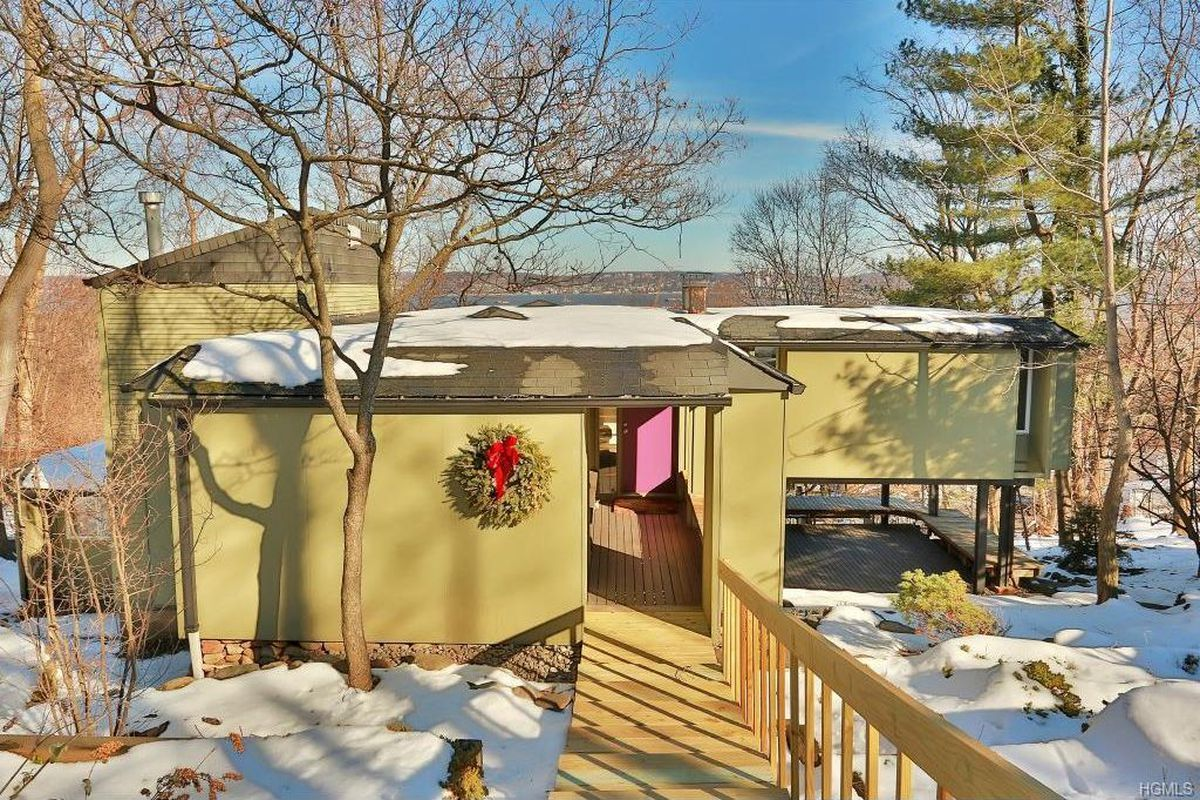 Exterior shot of an avocado-green wooden house with snow on the ground.