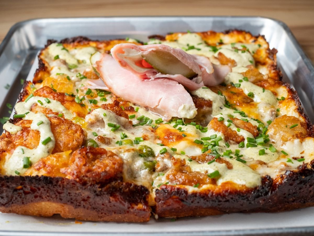 A rectangular pizza topped with tater tots, creamy sauce, an a pickle wrapped in ham garnish