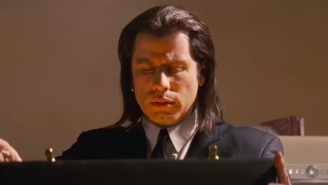 John Travolta looks down at a glowing briefcase in Pulp Fiction