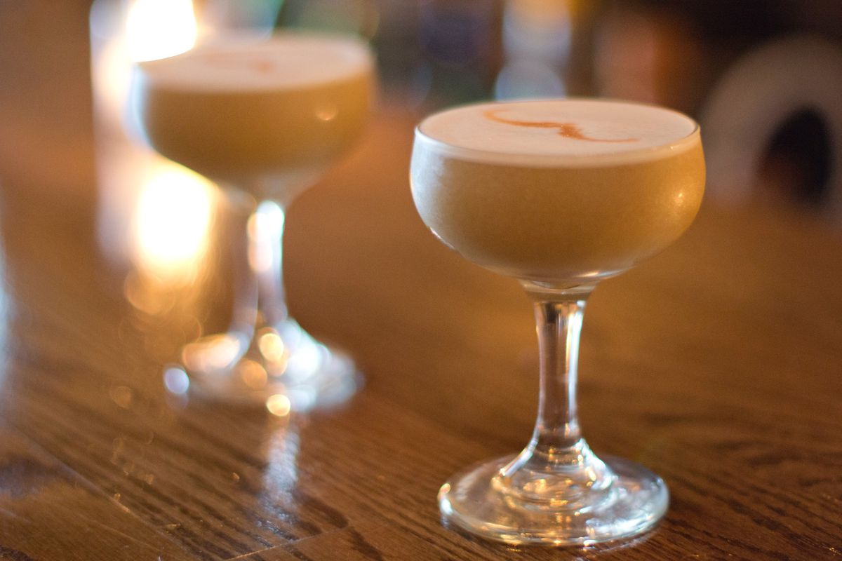 Two cocktails at Booker and Dax, photographed from the side, with an egg white top and a finish of bitters