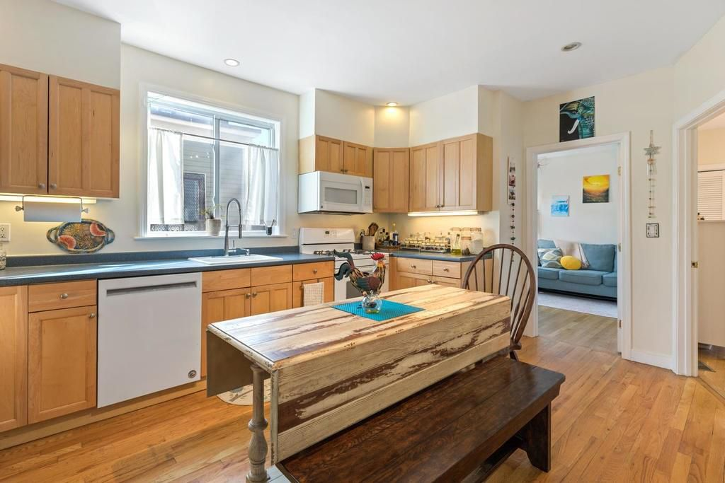 A kitchen with a long counter-slash-table in the middle.