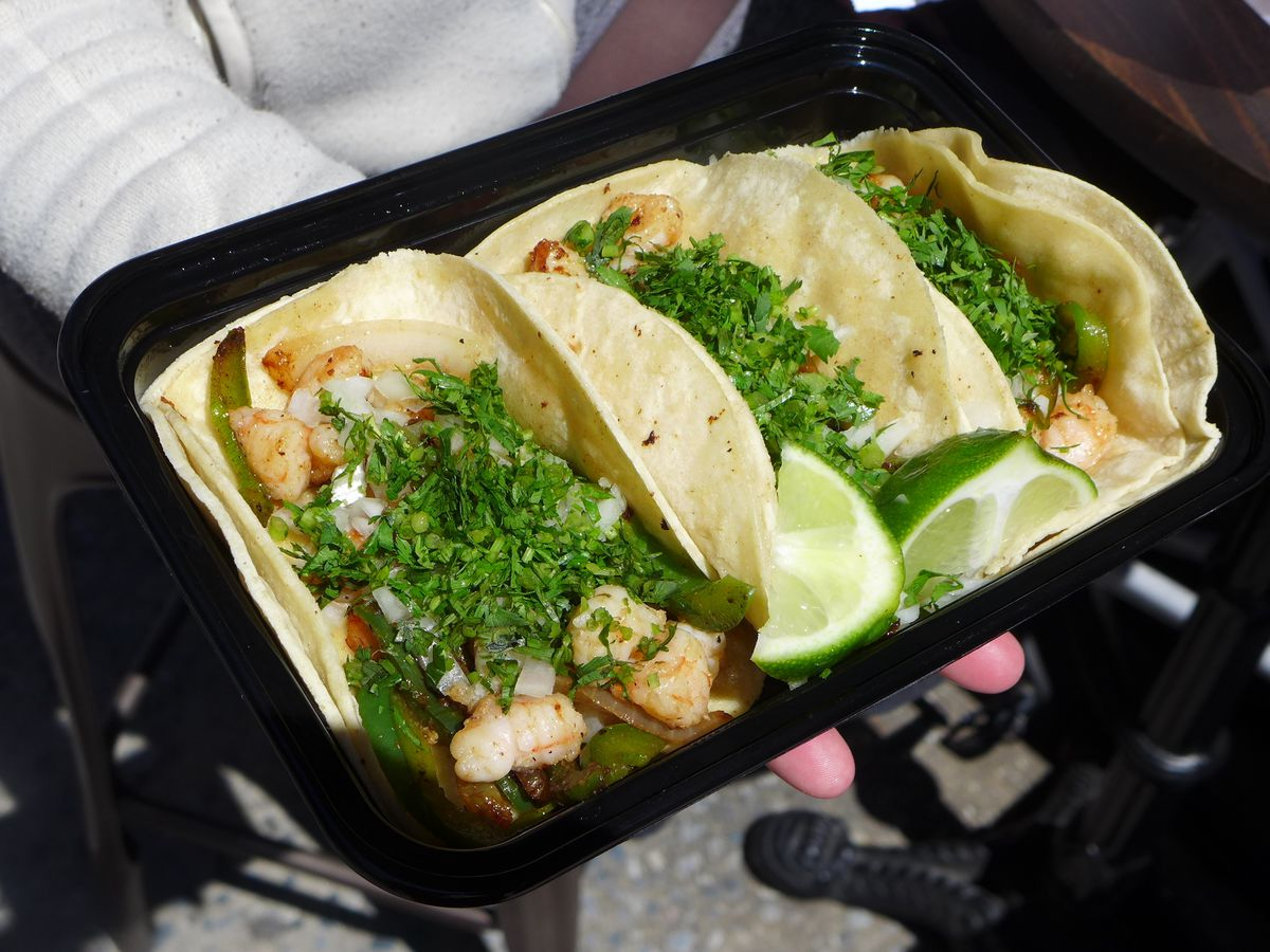 Three shrimp tacos heavily covered with cilantro held on the handlebars of a bicycle.