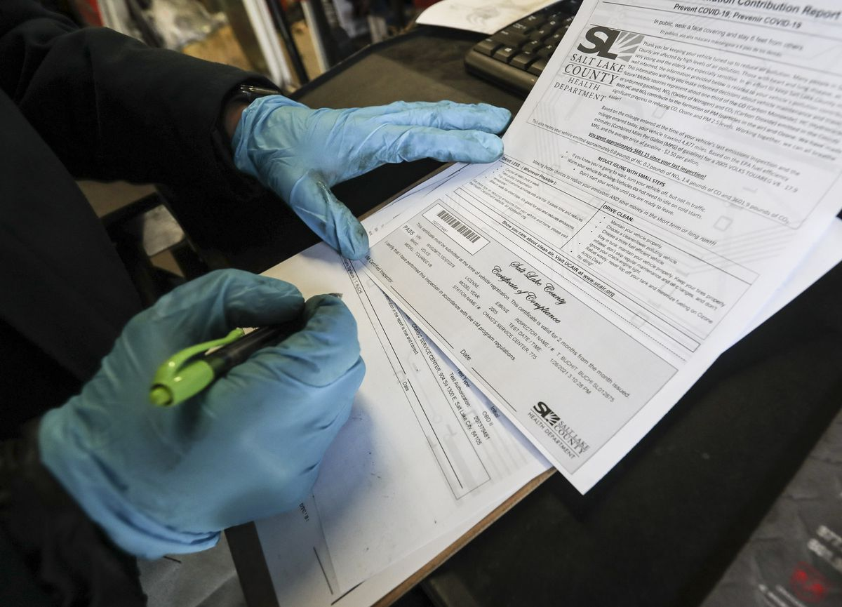 Teal Buchi fills out a certificate of compliance after performing an emission test at Craig's Service Center in Salt Lake City on Tuesday, Jan. 26, 2021.