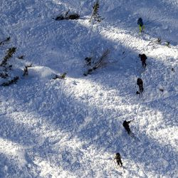 Skiers inspect an avalanche site in Little Cottonwood Canyon on Tuesday, Dec. 20, 2016. The avalanche occurred when two backcountry skiers descended the mountainside, prompting a response from Unified Police, Backcountry Rescue, Alta marshals and the DPS helicopter.