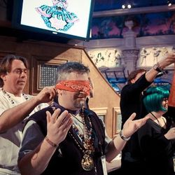 Chef John Besh blindfolding a contestant in the Krewe of Rocckus' drinks competition.