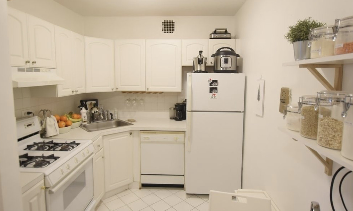 A kitchen with white cabinetry and white tiles.