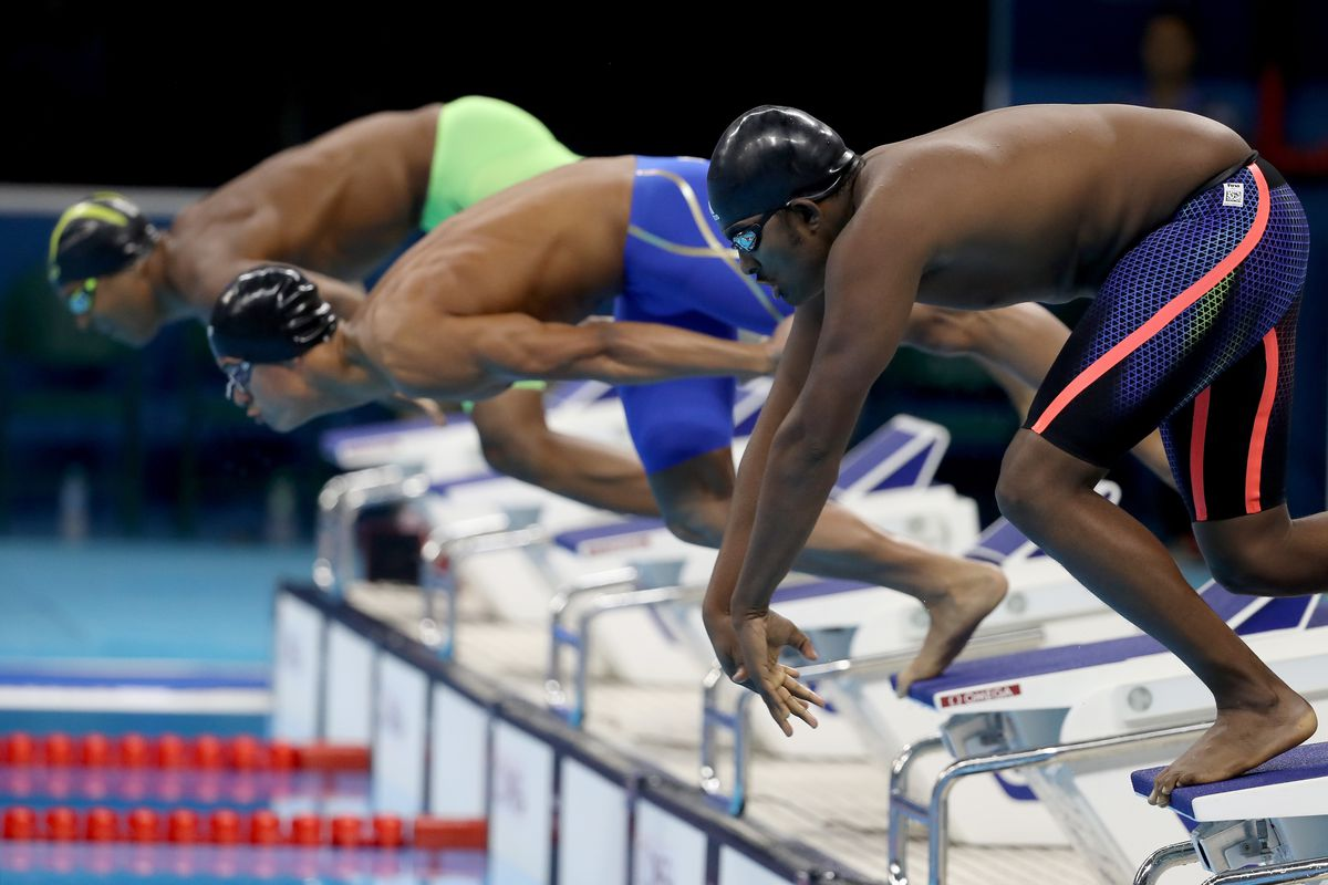 Robel Habte prepares to dive off the blocks into the pool at the 100-meter freestyle