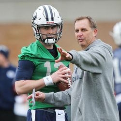 Brigham Young Cougars coach Ty Detmer talks with Brigham Young Cougars quarterback Tanner Mangum (12) during practice in Provo on Tuesday, March 1, 2016.