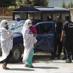 Pakistani women walk past the house where Osama bin Laden's family are being detained in Islamabad, Pakistan, on Monday, April 2, 2012, in Islamabad, Pakistan. The lawyer for Osama bin Laden's family says a Pakistani court has convicted his three widows and two of his daughters on charges of illegally living in Pakistan and sentenced them to 45 days in prison.