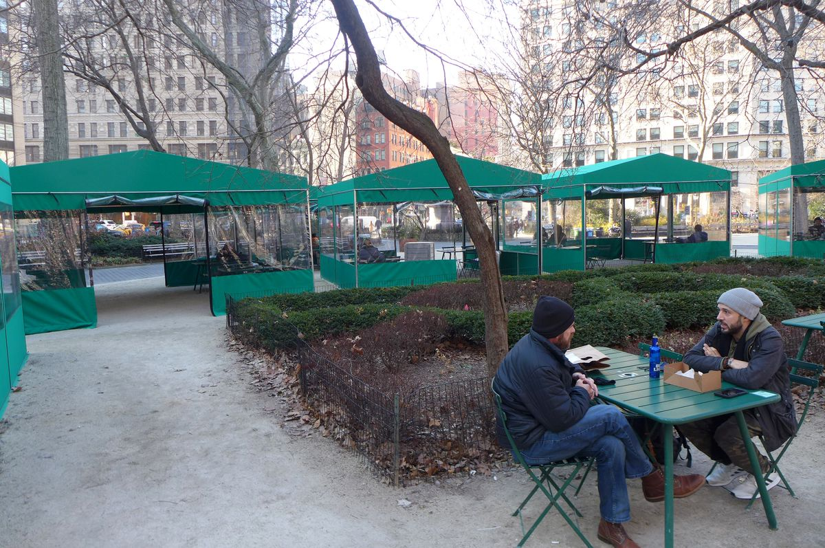 A table with two diners in a park setting in the foreground with several green dining tents in the background.