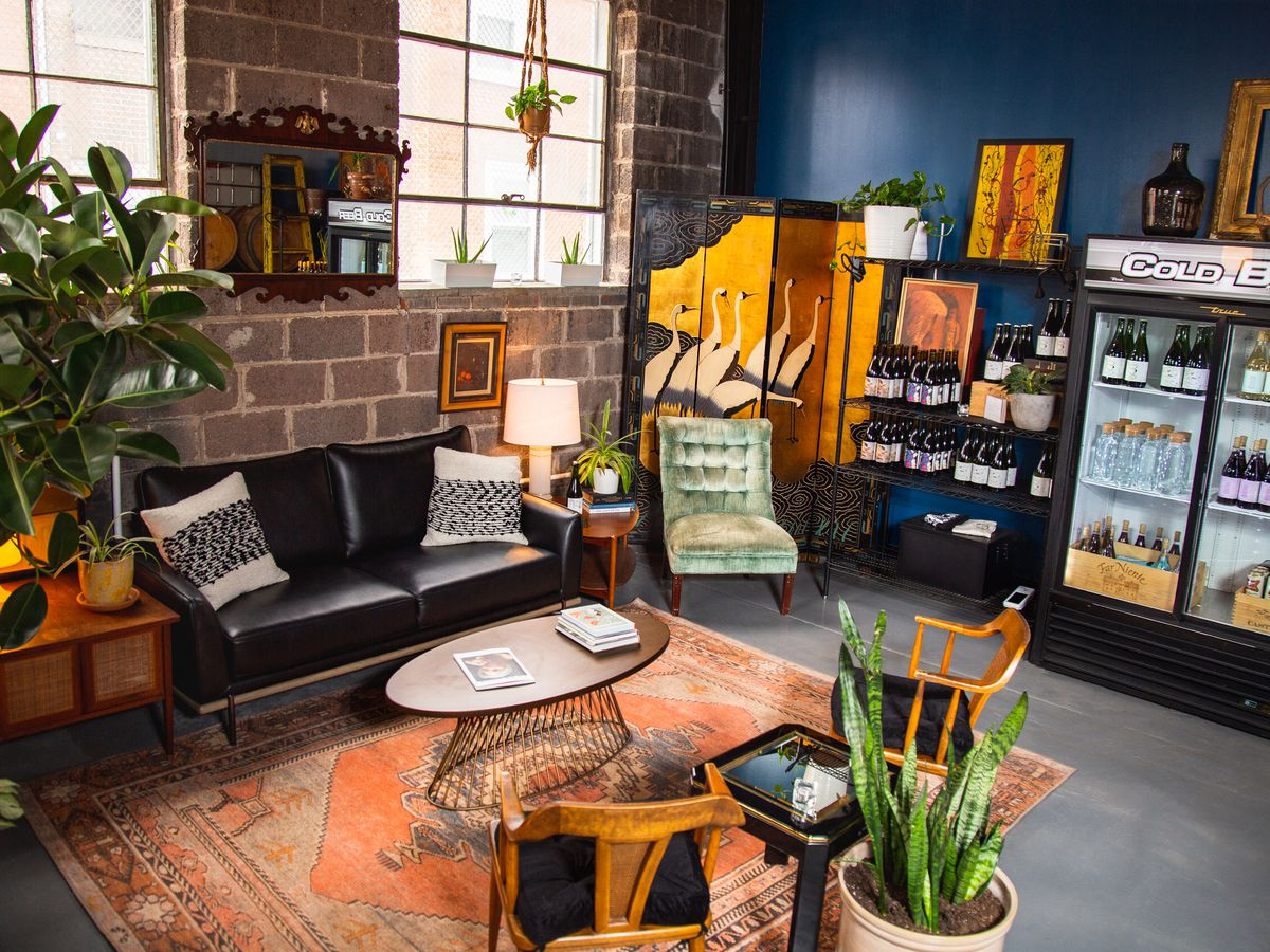the inside of mural city cellars with couches, coffee table, plants, and a fridge stocked with wine