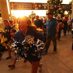 A cheerleader runs through the gate prior to the Utah-BYU game in Provo on Saturday, Sept. 9, 2017.