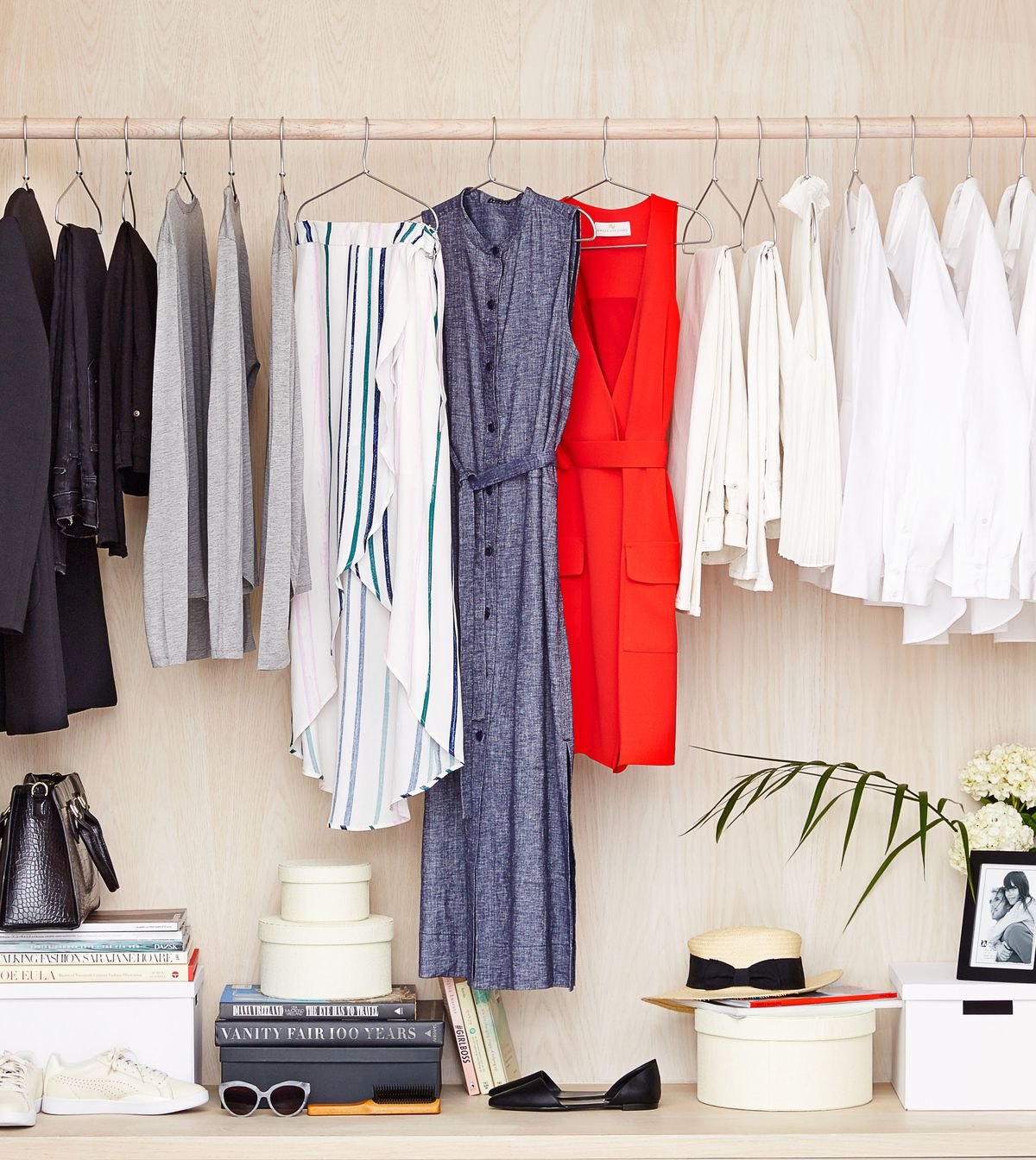 A closet with clothes hanging from the hanger bar